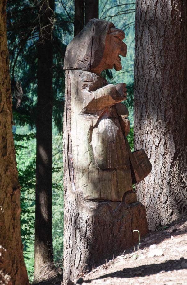 Geschnitzte Figuren am Wegesrand begleiten uns auf der Wanderung.